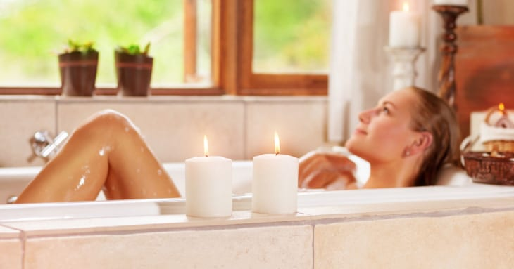 Woman in bath with candles next to tub